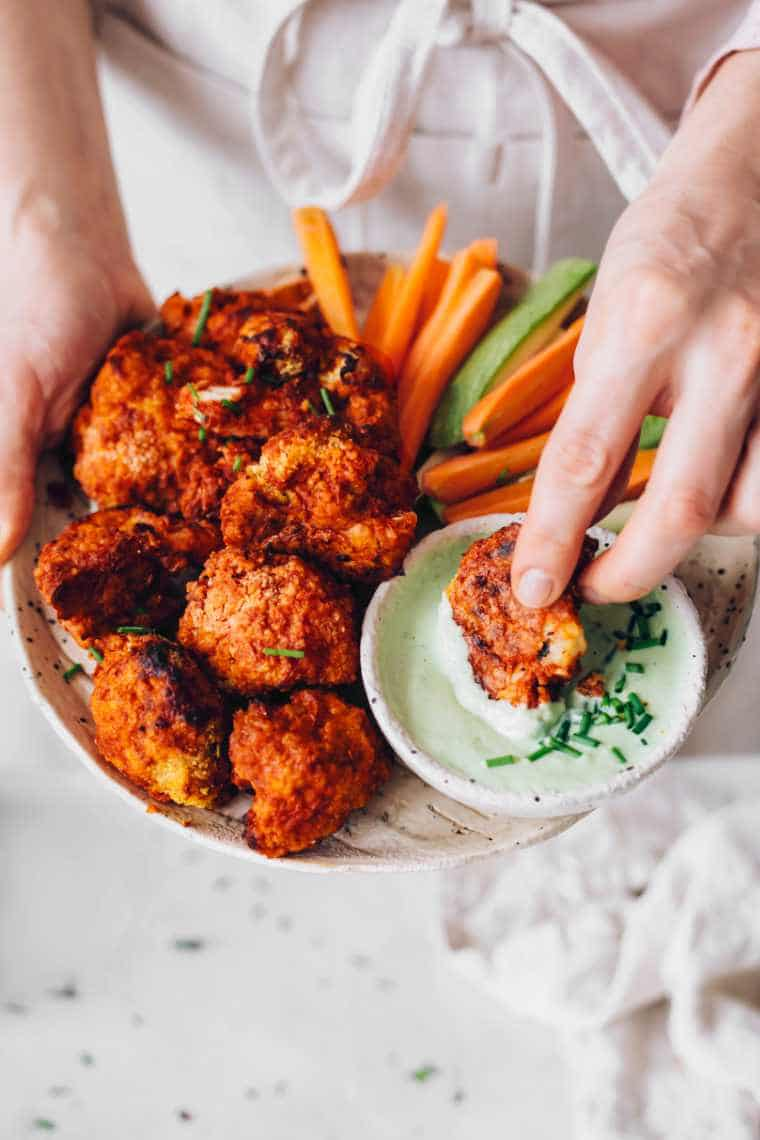 woman in apron holding a white plate with buffalo cauliflower while dipping one of the florets into a vegan ranch