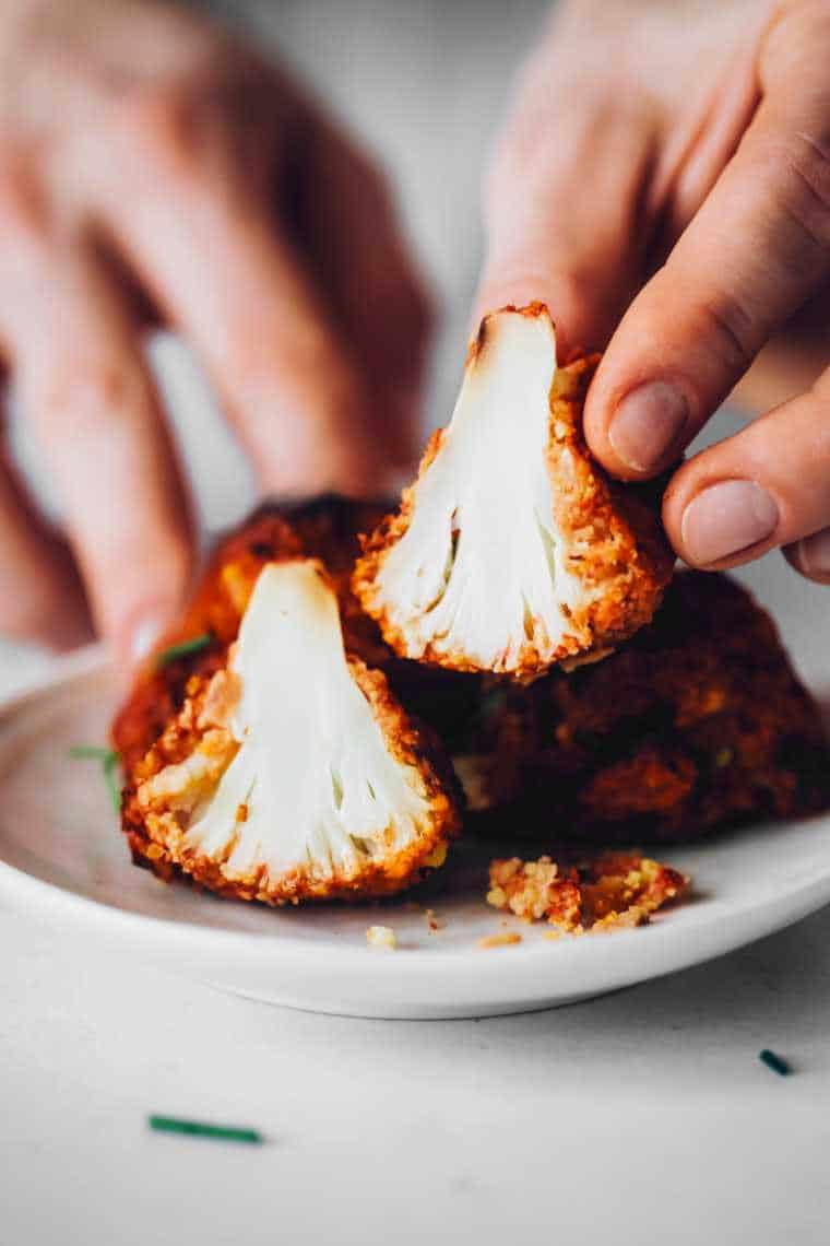 vegan cauliflower buffalo bite cut open and a hand showing the texture on the inside