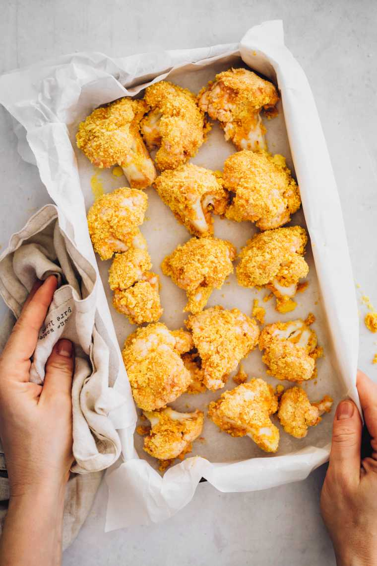 uncooked vegan cauliflower buffalo wings on a baking dish with parchment paper
