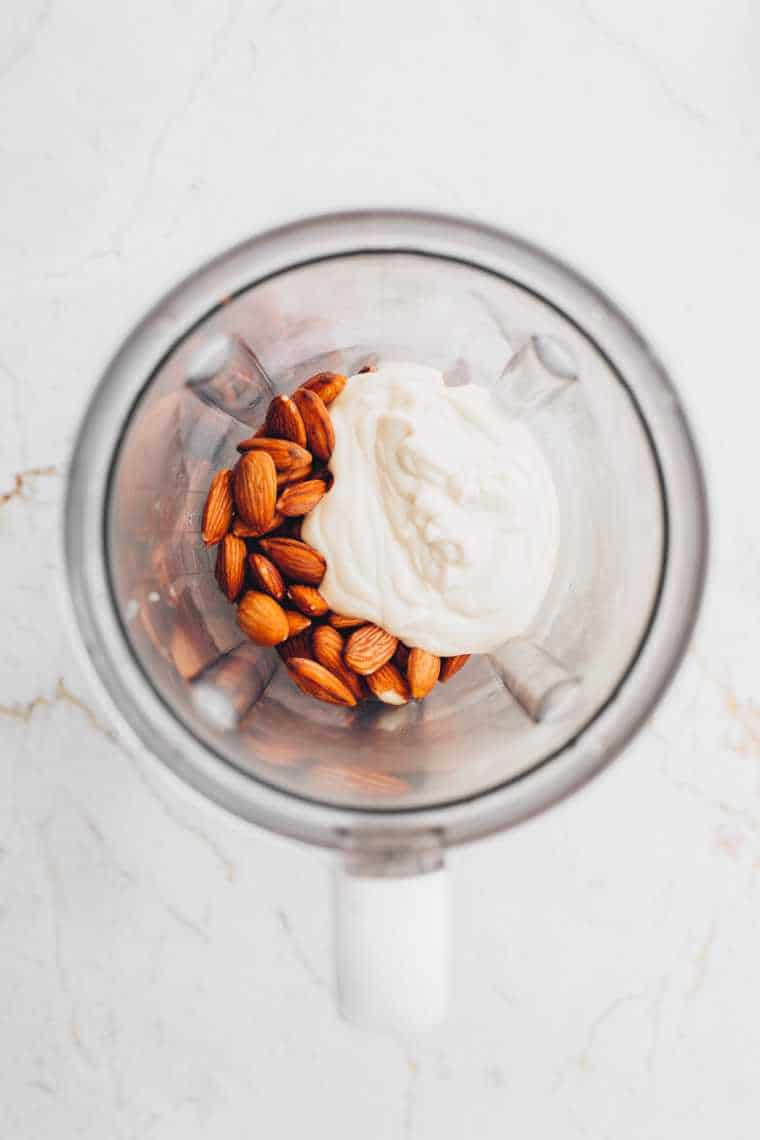 almonds and vegan cream cheese in blender jar on a table