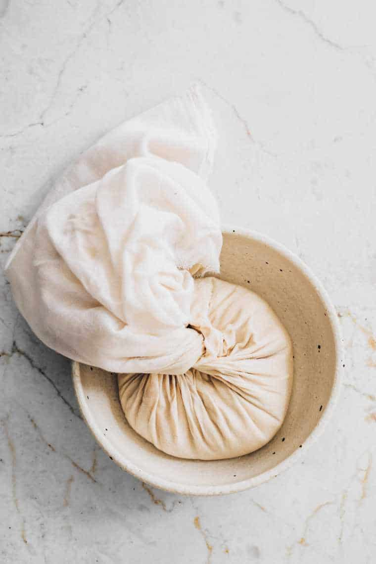 white bowl on a table with a cheesecloth holding almond mixture