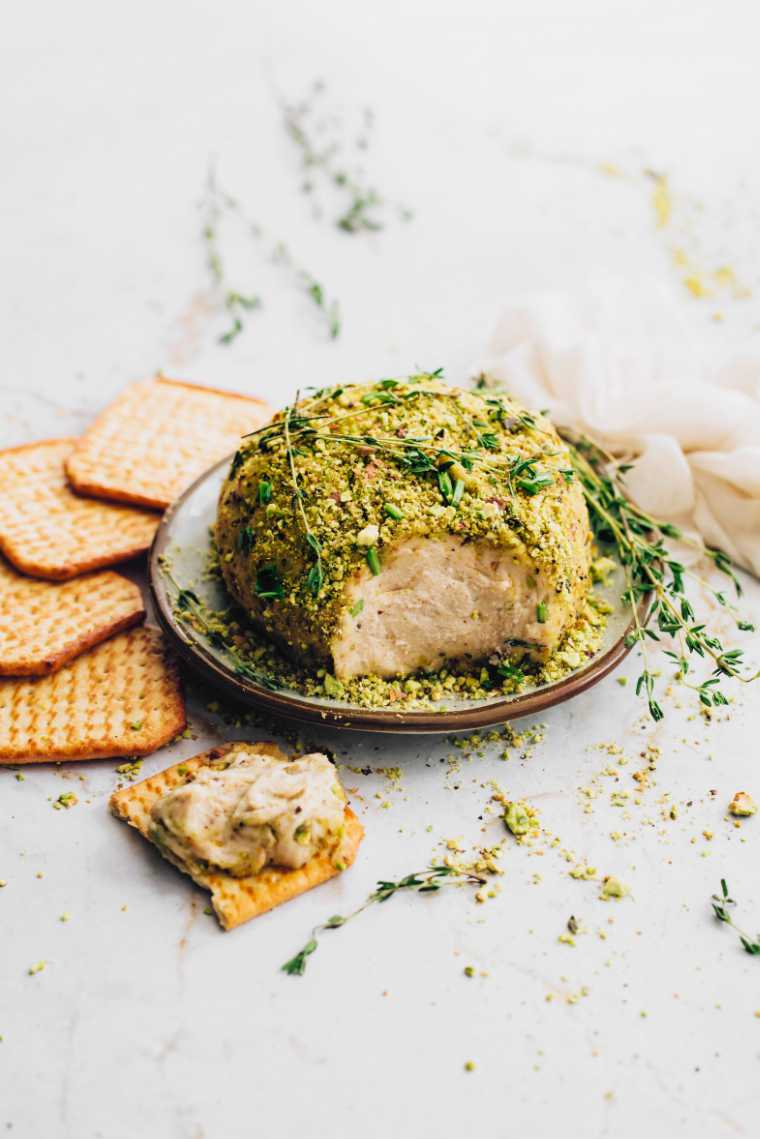 small white plate with a vegan almond cheese ball with herby crust next to some crackers