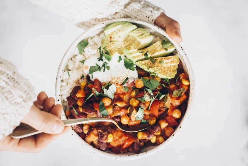 Top view of woman holding bowl filled with rice, bean chili, sliced avocado, vegan yogurt and sprinkled herbs