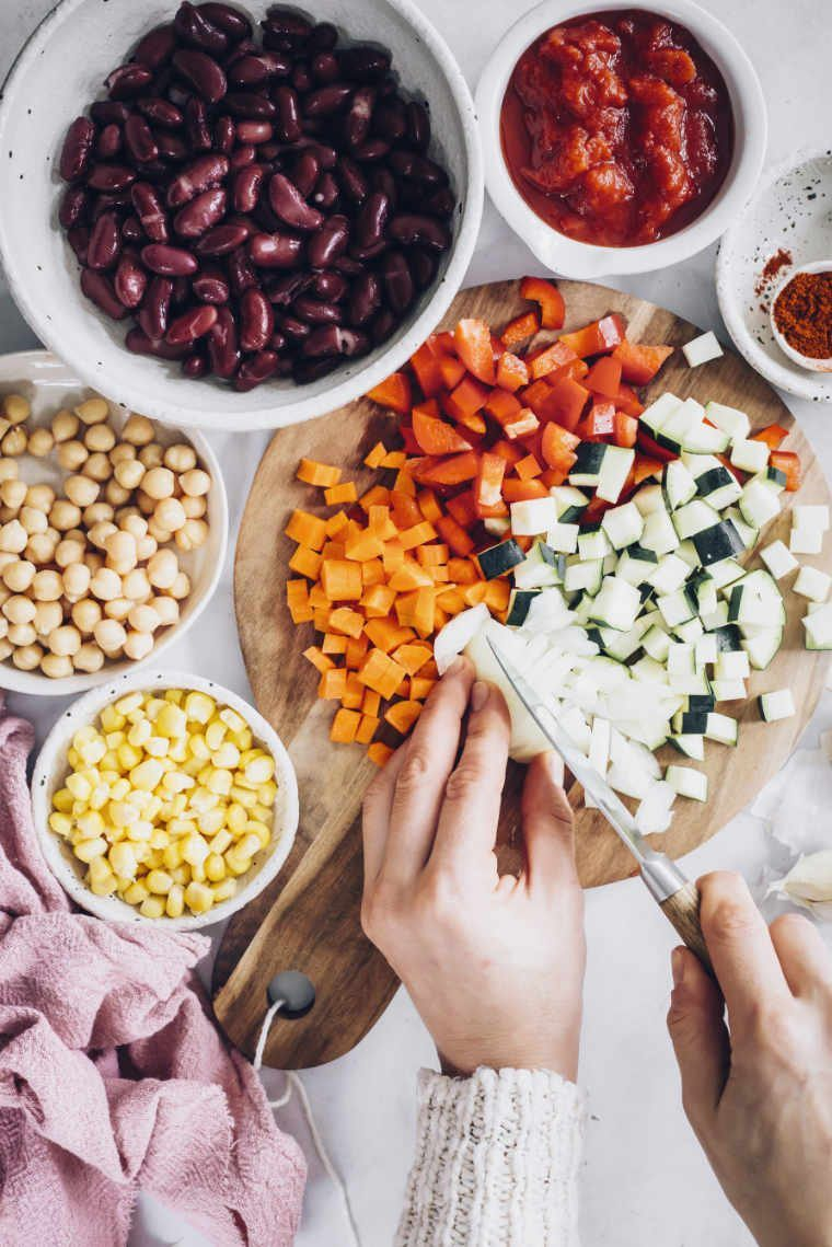 Top view of woman cutting colorful vegetables an a wooden board with beans, corn and tomato paste placed in small bowls