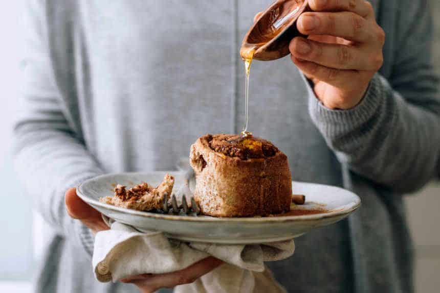 woman in grey sweater holding a white plate with a vegan whole wheat cinnamon roll and pouring maple syrup over it