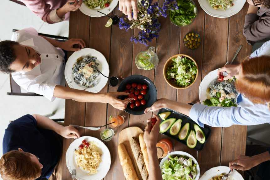 wooden table with several people enjoying food and drinks during a vegan cookout