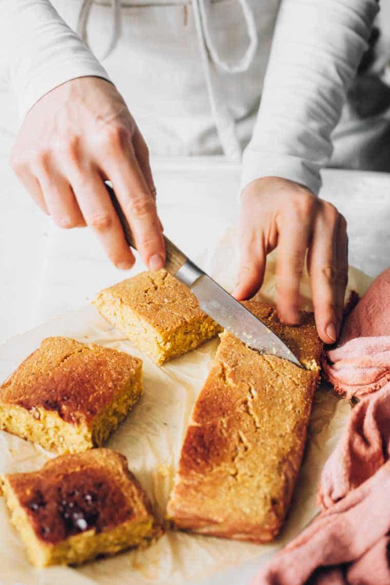 Woman with white apron cutting freshly baked cornbread into six equal squares