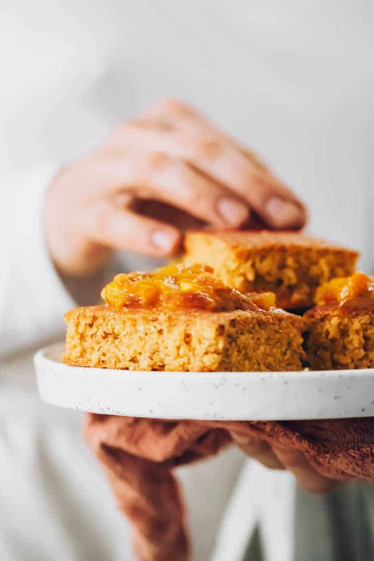 Close up of woman holding plate with stacked vegan gluten-free cornbread topped with mango chutney