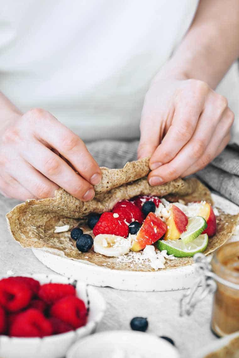 woman standing by a table with a plate of whole grain vegan crepes and filling it with fruit