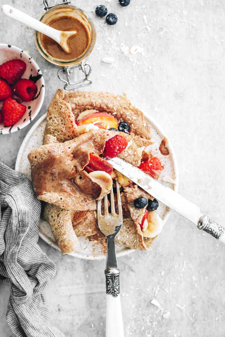 top view of a white plate with whole grain vegan crepes and fruit topped with some cutlery