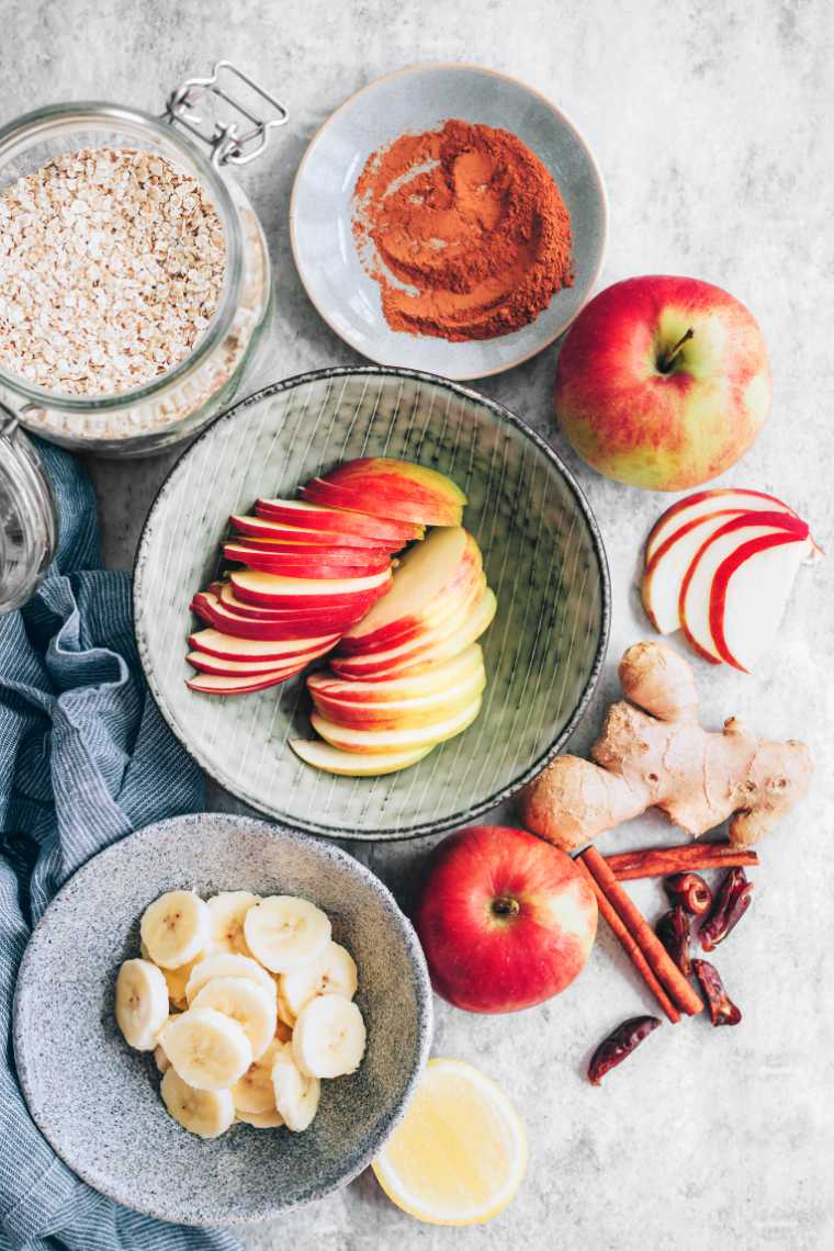 table with a jar of oats, fresh apple, apple slices, banana, ginger, dates and cinnamon