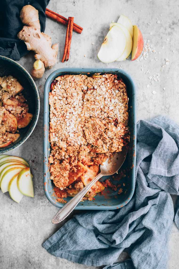 grey table with a towel, apple slices, cinnamon, ginger and a baking dish with baked vegan crumble