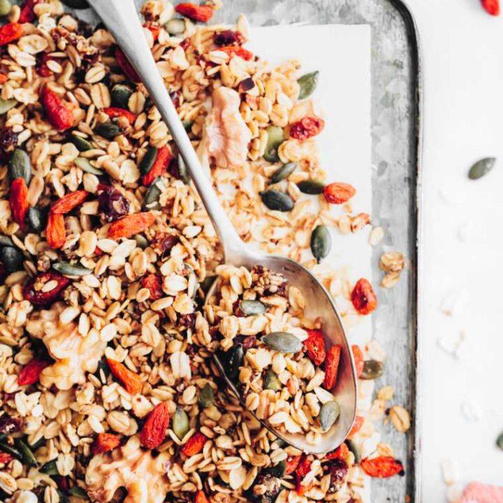 baking tray with homemade crunchy vegan granola make with dates, cinnamon, goji, walnuts and pumpkin seeds