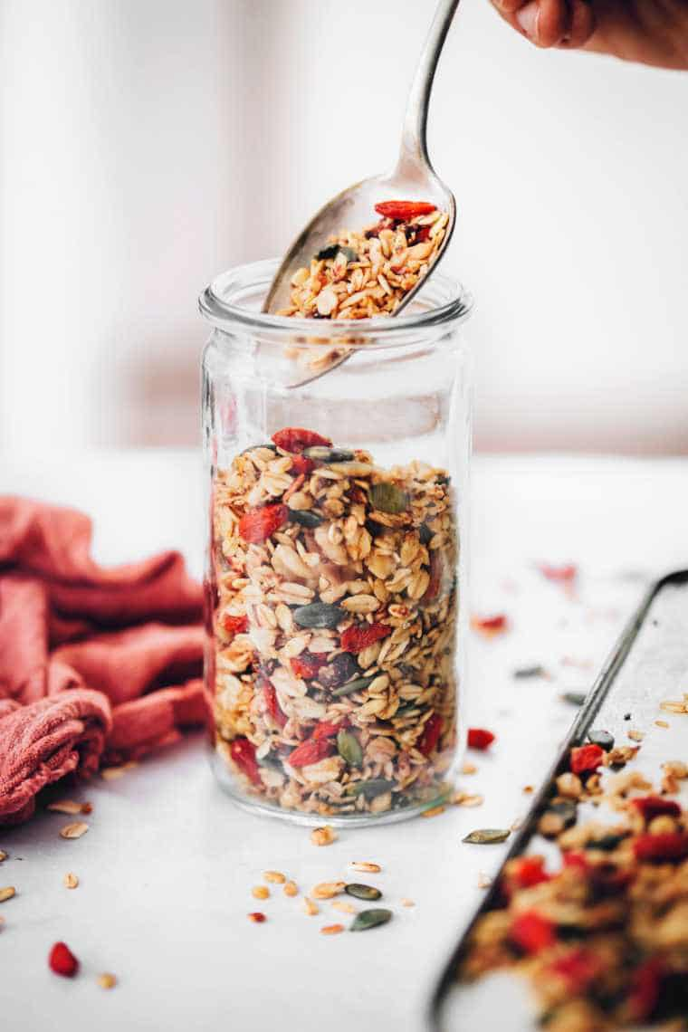 glass jar in which freshly baked vegan date granola is being put with a spoon for meal prep