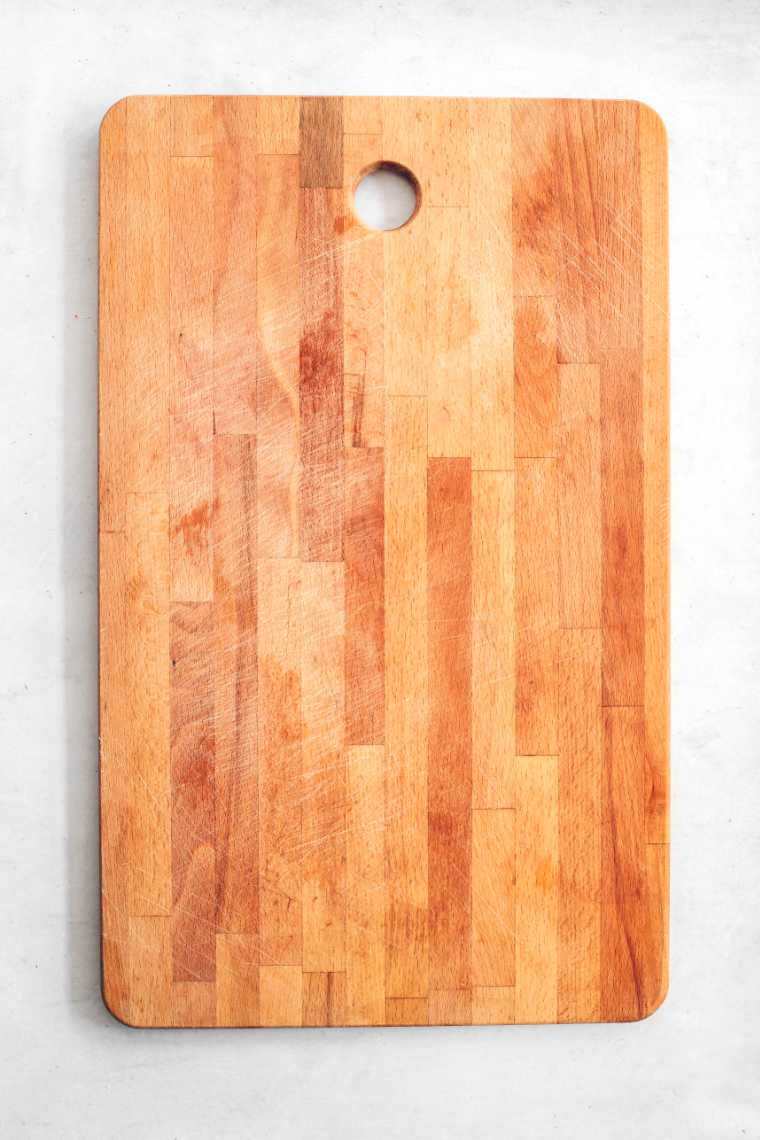empty wooden cutting board on white surface