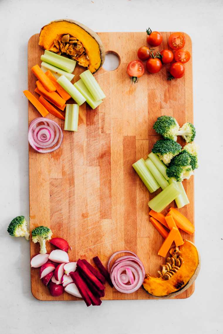 wooden appetizer platter with colorful veggies such as roasted pumpkin, fresh tomatoes, broccoli and carrot sticks