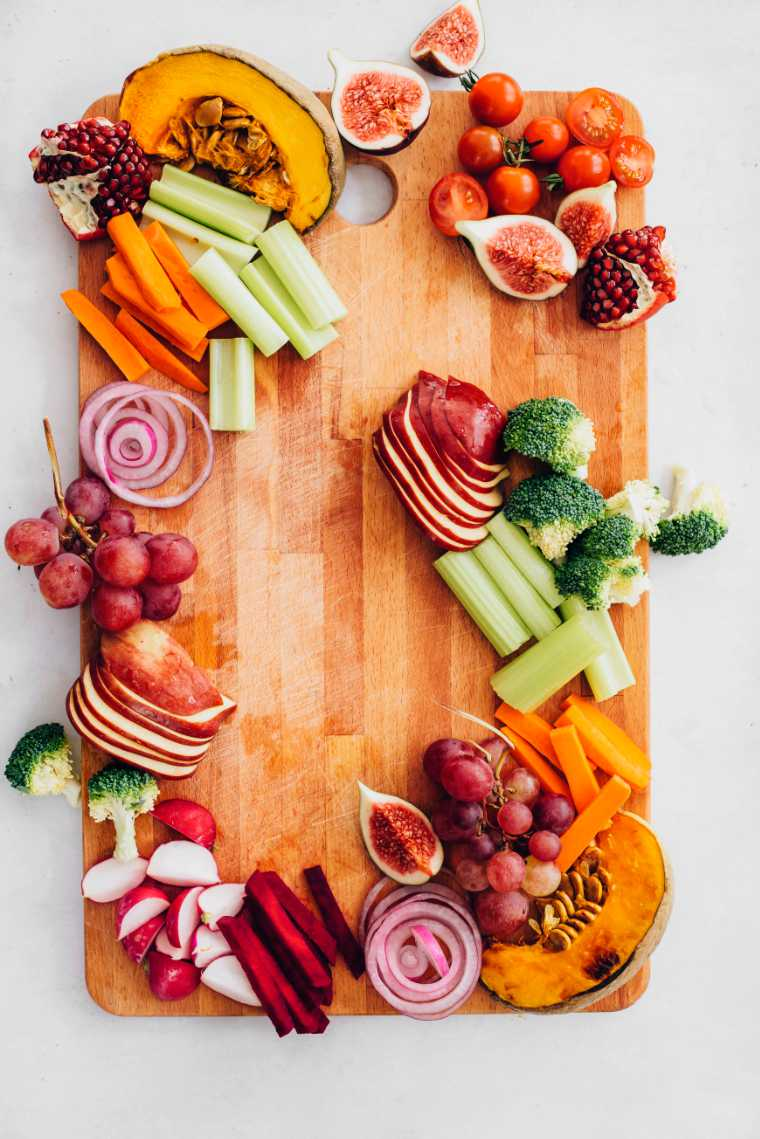 wooden appetizer platter with raw veggies, figs, pomegranate, grapes and roast pumpkin