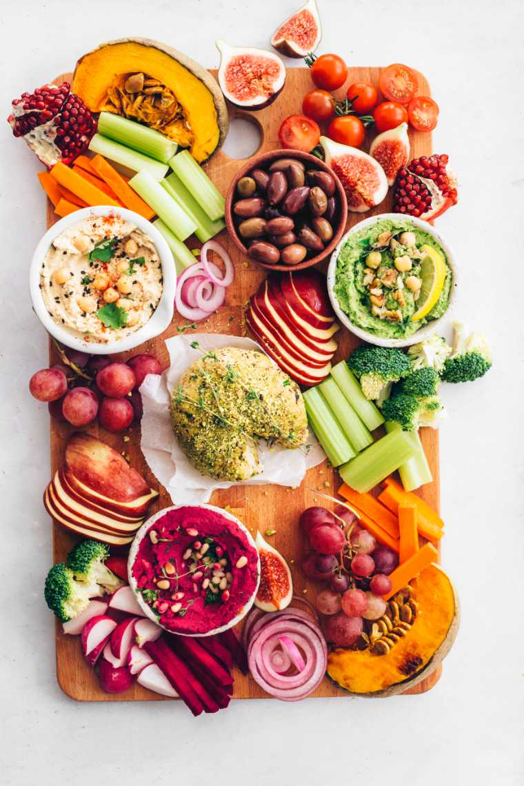 wooden board with colorful fruits and vegetables, hummus and vegan cheese