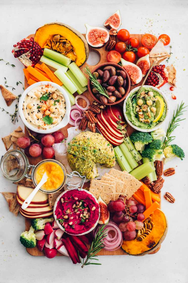 colorfully loaded board with crackers, fall produce, 3 types of hummus and nut cheese