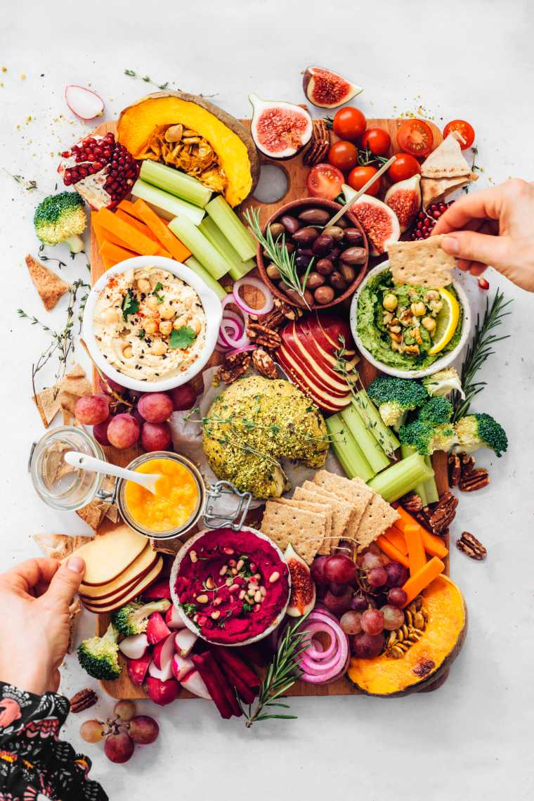 two hands reaching for parts of a colorful vegan fall appetizer platter with hummus and cheese