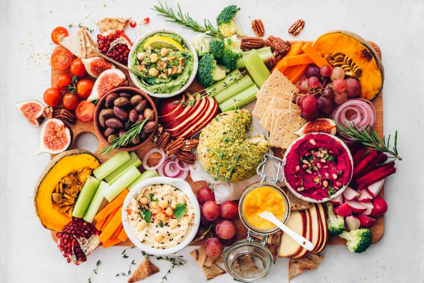 colorful vegan appetizer platter with crackers, fall produce, 3 types of hummus and nut cheese