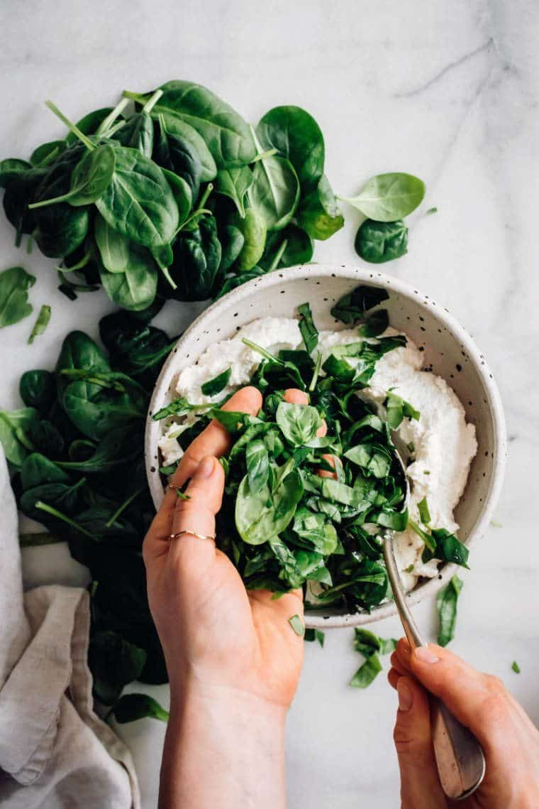 white bowl with almond ricotta in which fresh spinach is mixed by two hands