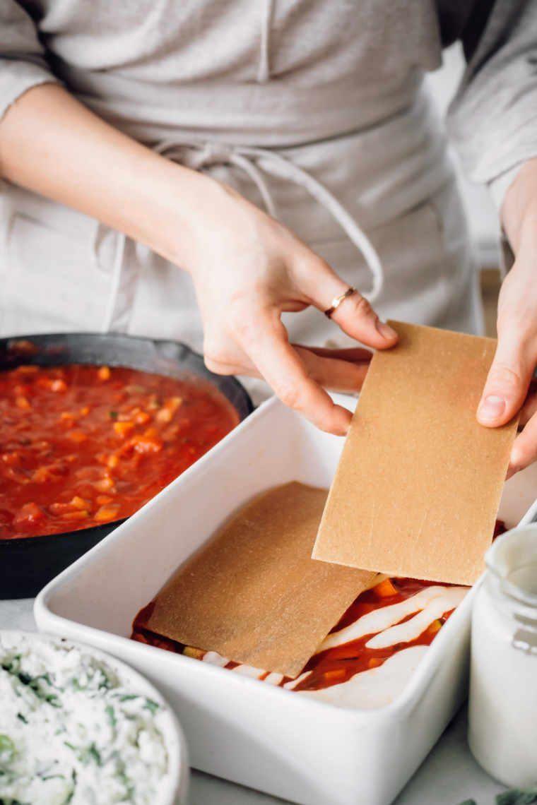 woman layering vegan lasagna by placing whole grain sheets on top of tomato sauce