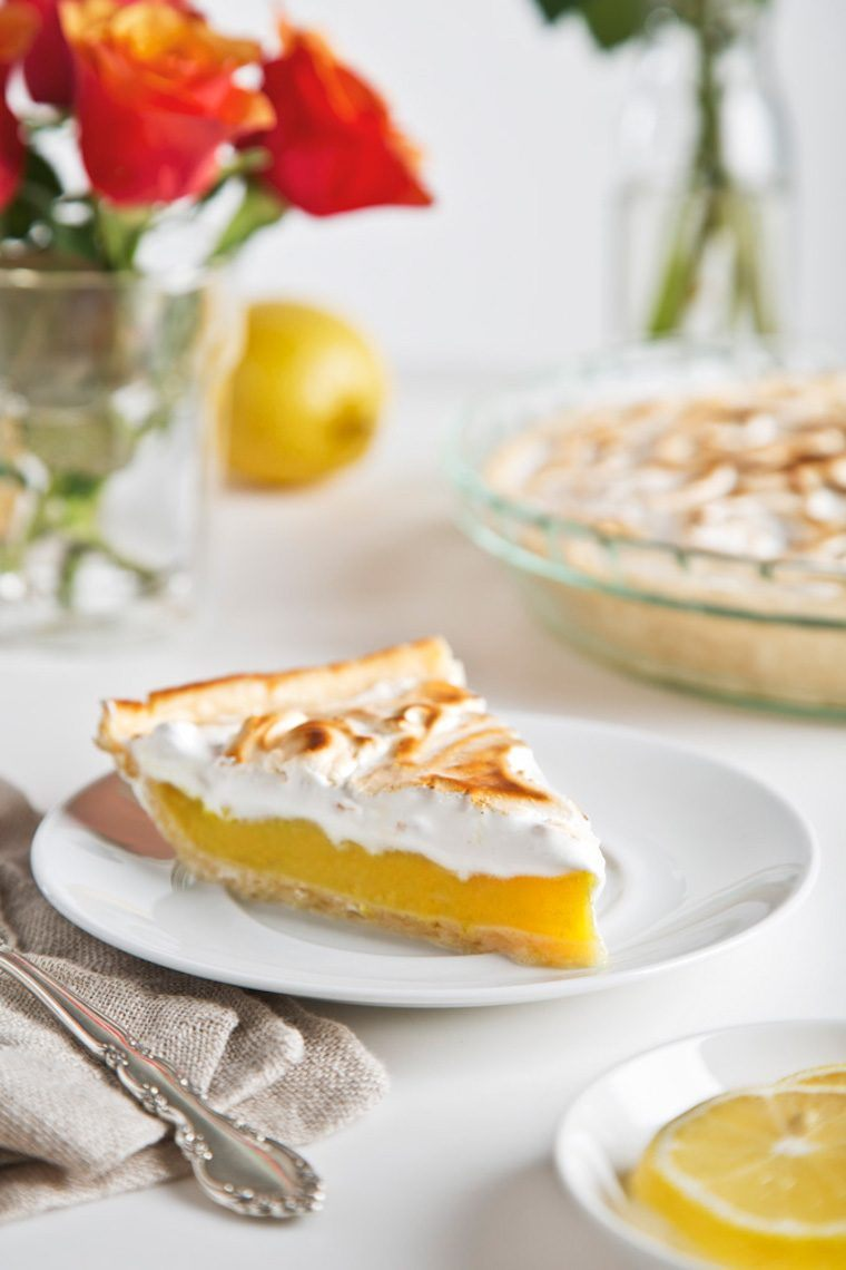 slice of vegen lemon meringue pie on a plate standing on a table with the whole pie and flowers