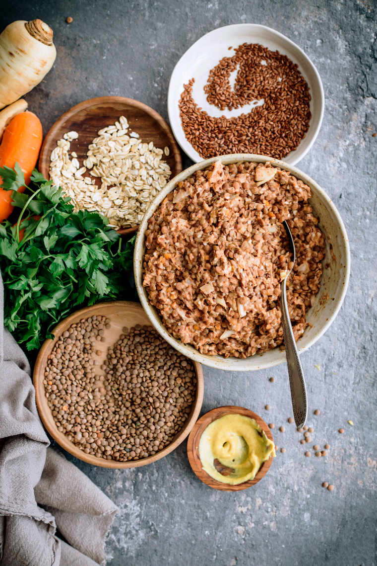 different sized bowls on a grey surface with ingredients for a vegan lentil loaf such as lentils, oats, flax and mustard