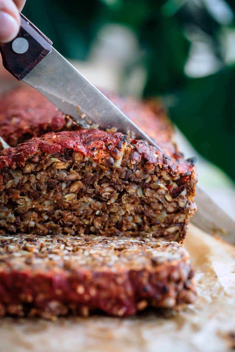 hand holding a knife and slicing vegan meat loaf on a chopping board