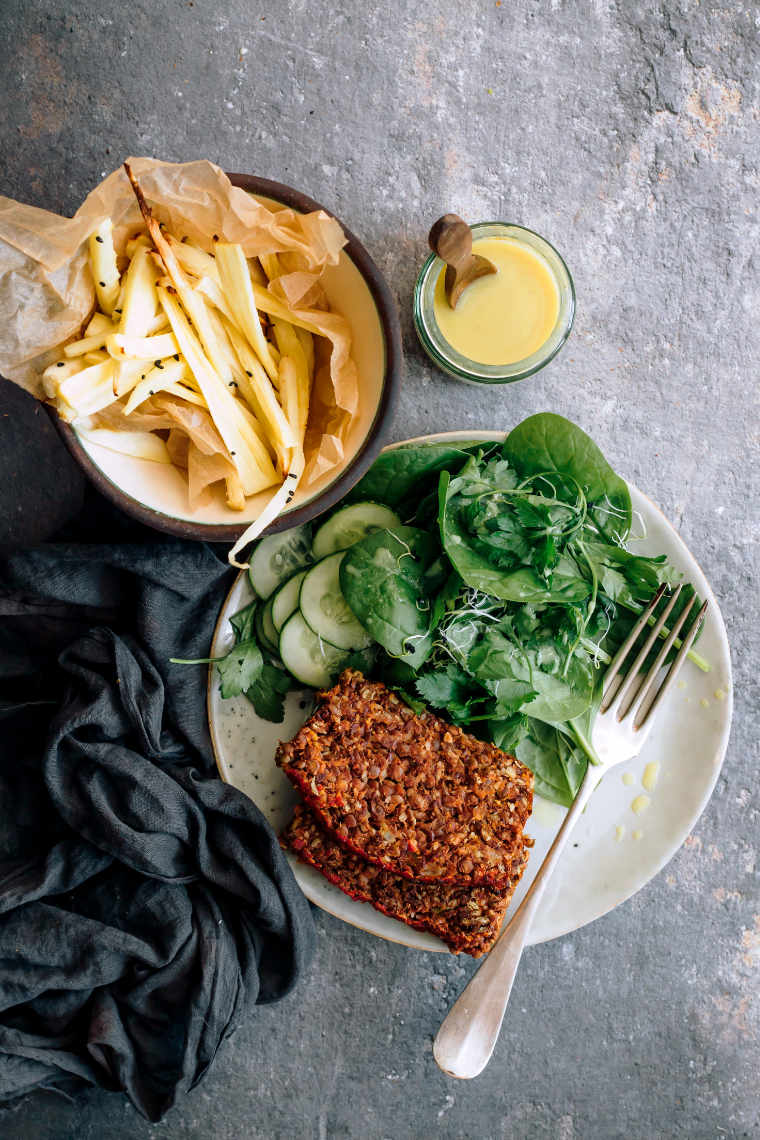 white plate with green salad, two slices of lentil loaf and a fork next to some parsnip fries