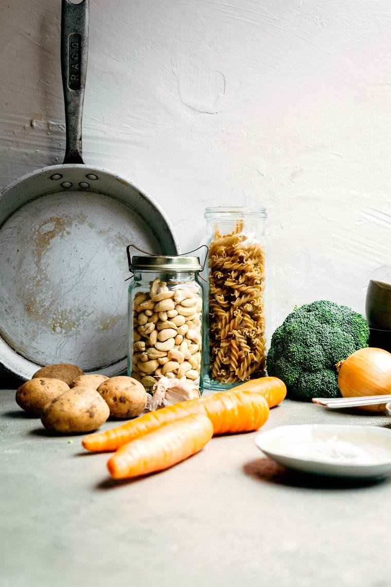 carrots, broccoli, potatoes, cashews and whole grain pasta next to a pan on a table