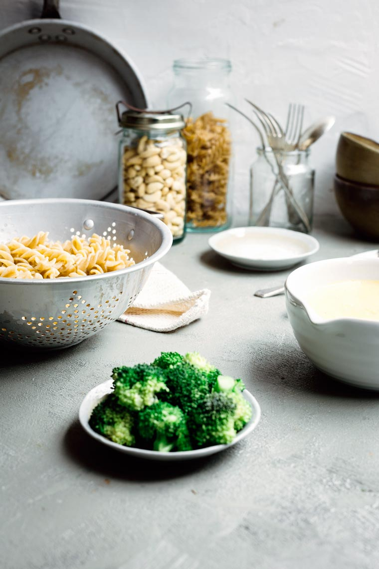plate of broccoli florets along with cooked vegan pasta and dairy-free cheese sauce on a table