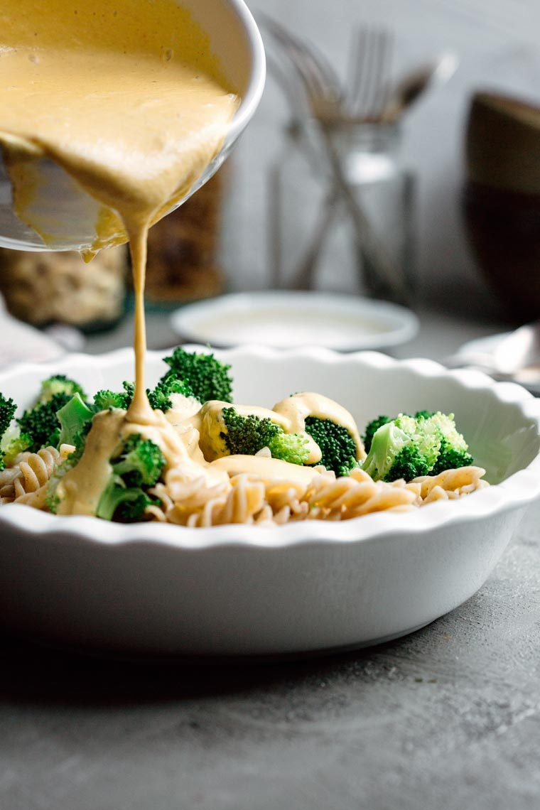 pasta and broccoli in a white bowl over which plant-based homemade cheese sauce is poured
