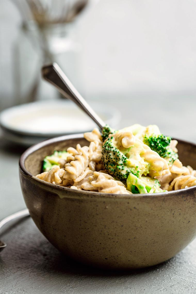 close-up of a bowl with whole food plant-based mac and cheese with broccoli and a spoon
