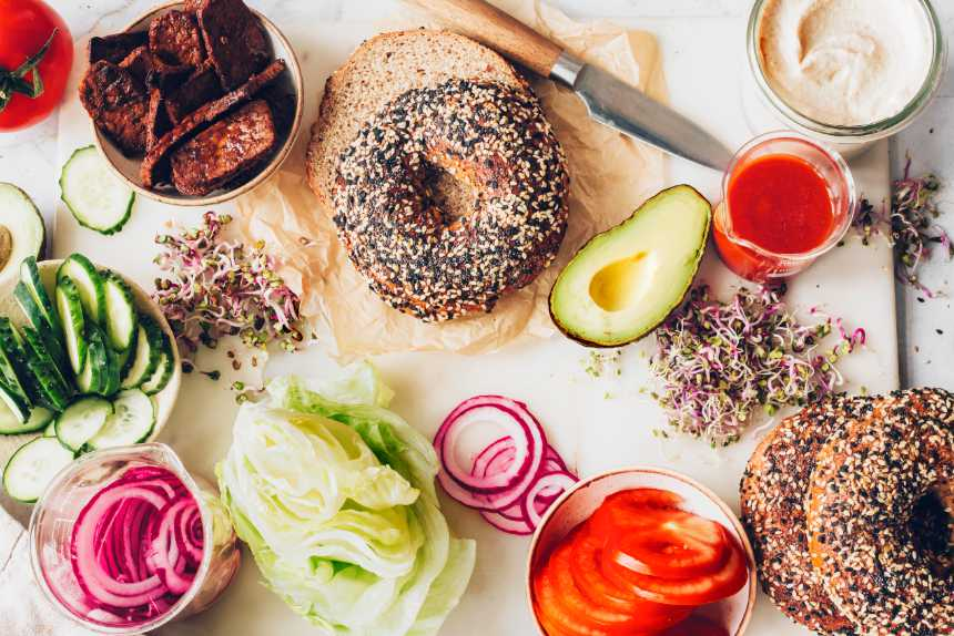 white cutting board with bagels, avocado, lettuce, red onion, tempeh and vegan cream cheese