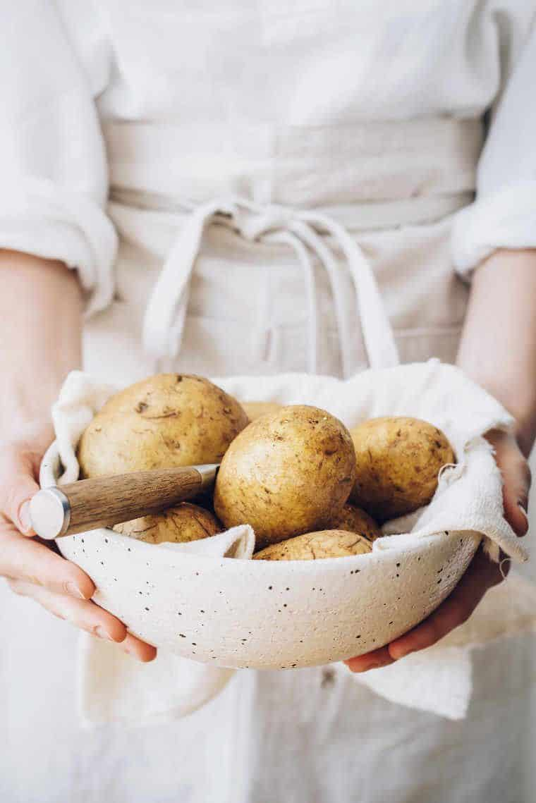 woman in white linen apron and shirt holding a white bowl of whole potatoes in her hands