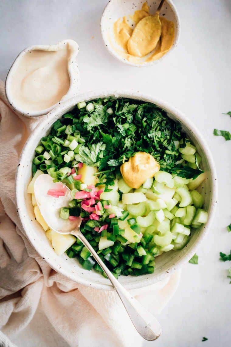 bowl with cooked potatoes, celery, parsley, pickles, mustard and radishes on a white surface