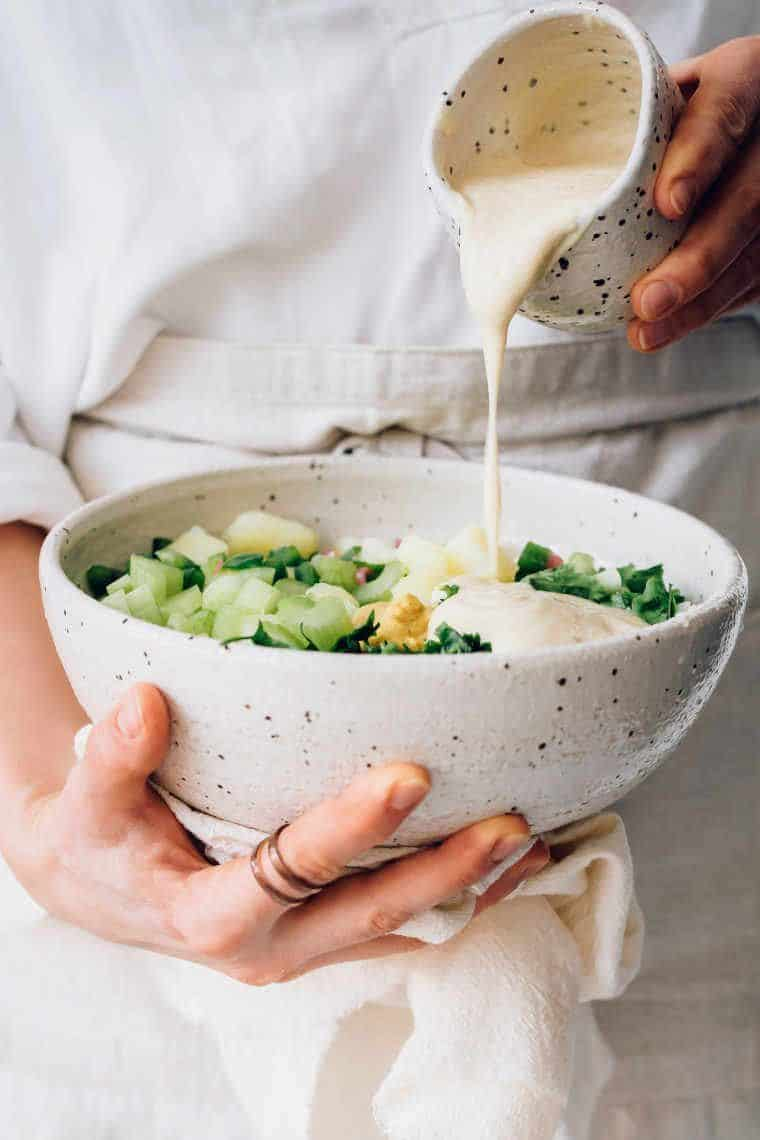 woman in linen apron holding bowl of potato salad in one hand and pouring cashew mayo over it with the other