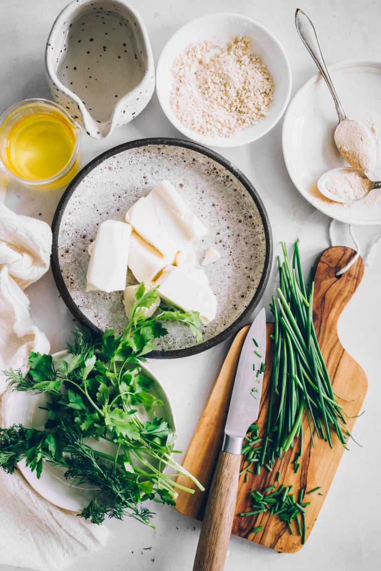 white table with different small bowls containing fresh herbs, silken tofu, vinegar and spices to create dairy-free ranch dressing
