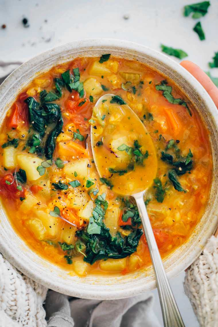 close up of a bowl with vegan red lentil carrot soup, spinach, vegetables and a spoon