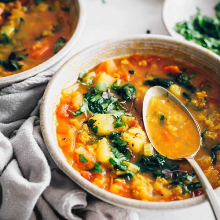Close up of two bowls of cooked vegan red lentil soup, garnished with green herbs and spoon lying on one bowl