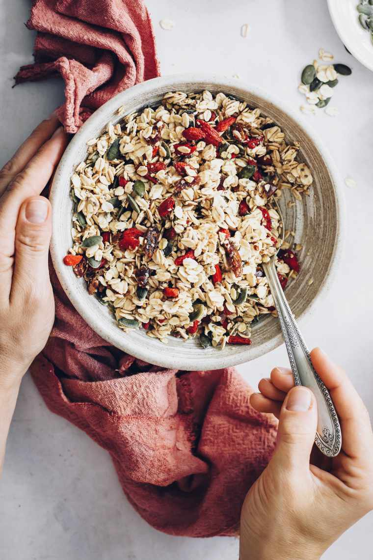 vegan pantry foods (oats, dried fruit, nuts and seeds) in a white bowl in which a woman places a spoon