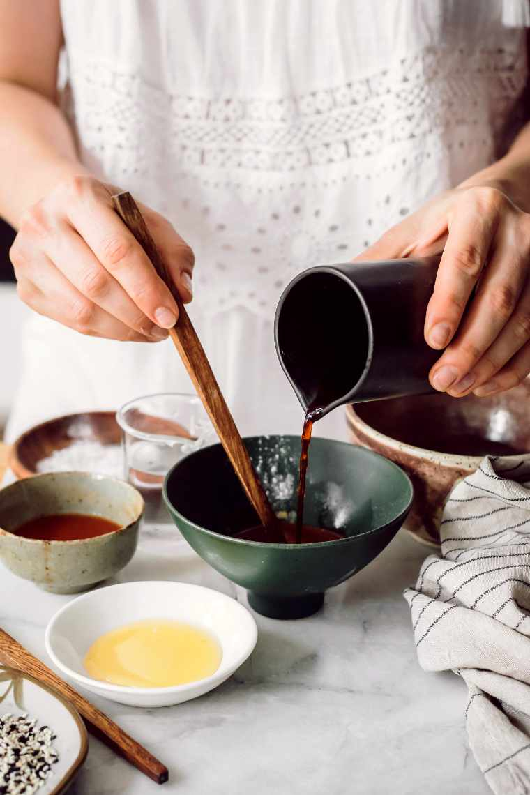 woman in white dress pouring soy sauce in a small bowl