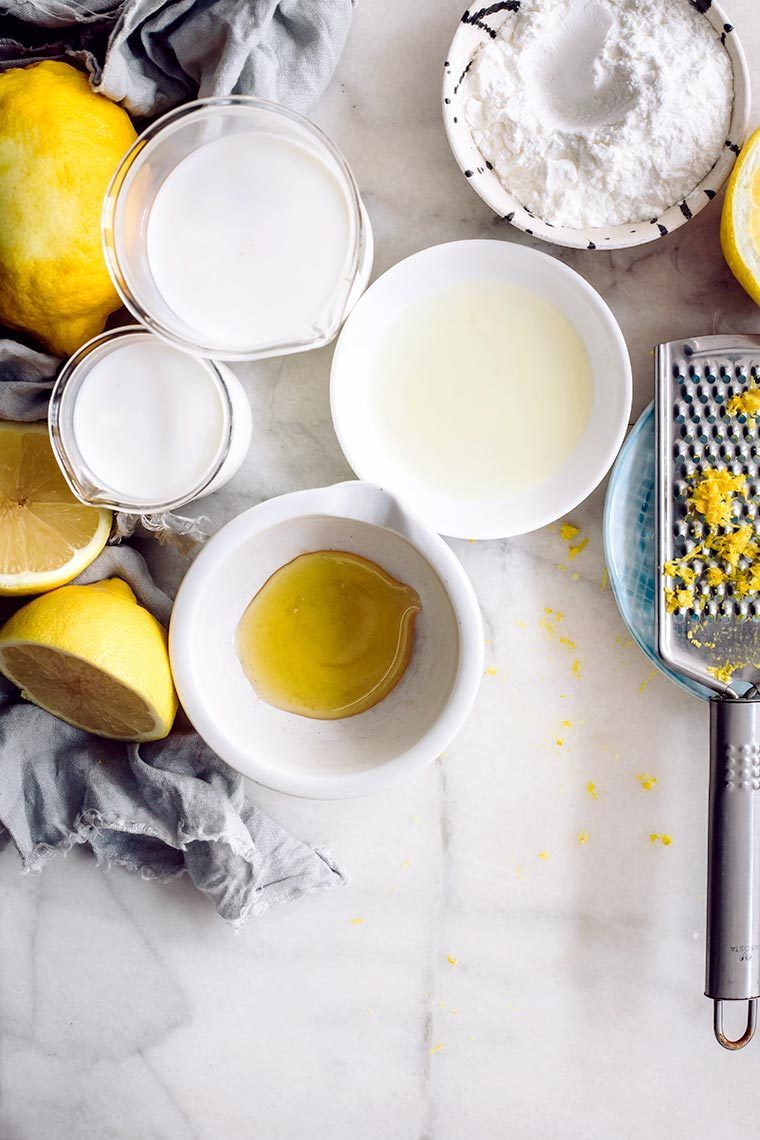 white table with some lemons and several small bowls containing plant based milk, sweetener and vanilla
