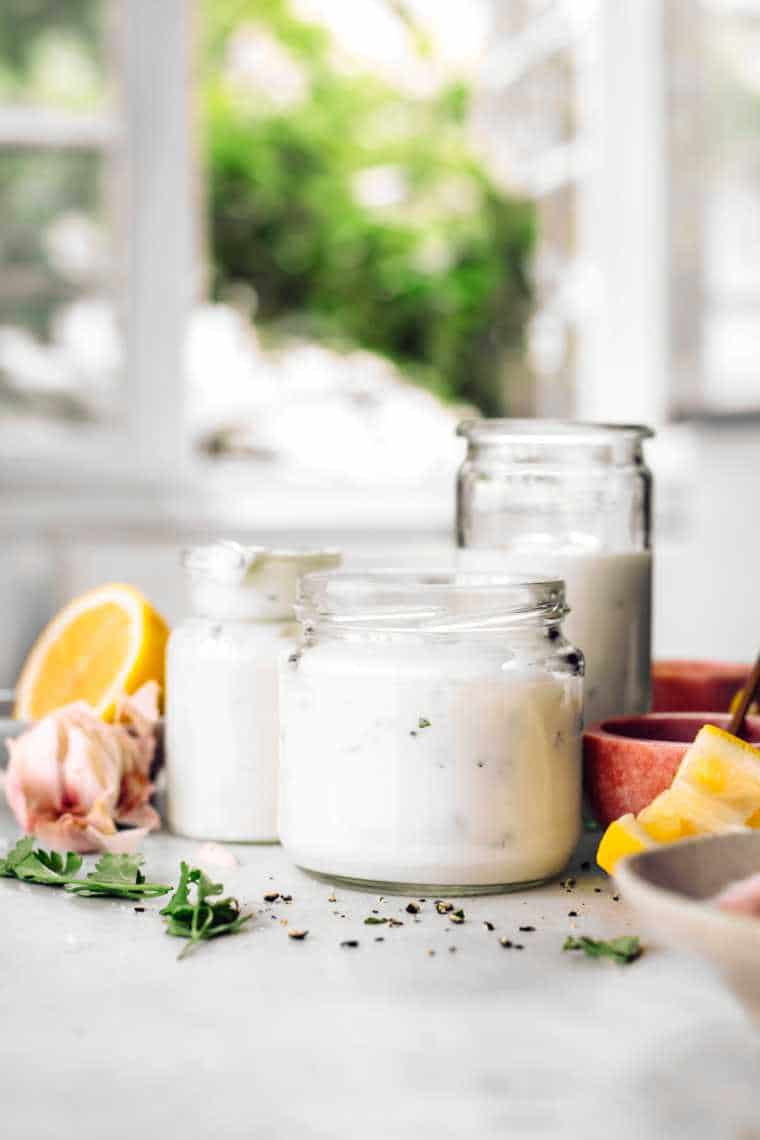 white table next to a window with three glass jars containing homemade vegan garlic yogurt sauce