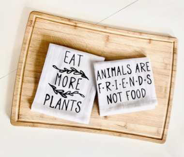 Two white kitchen towels with vegan message on top of a wooden chopping board