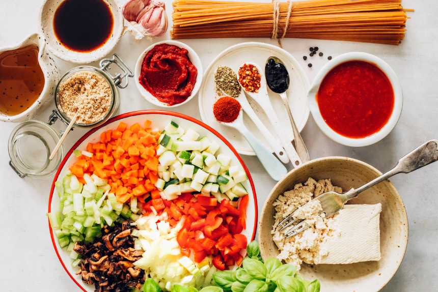 White table with whole-grain spaghetti, tofu, colorful chopped vegetables, tomato sauce and herbs