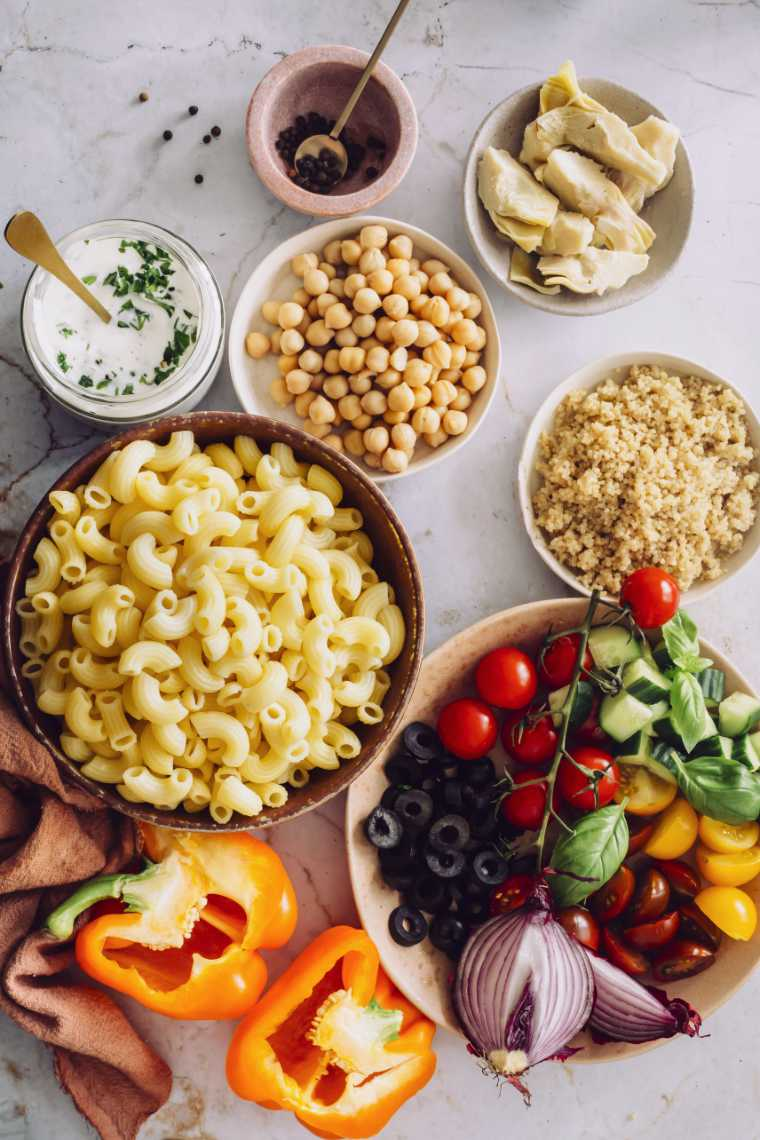 white table with different sized bowls containing plant-based weight loss foods like white dry pasta, cooked quinoa, cooked chickpeas and colorful raw vegetables