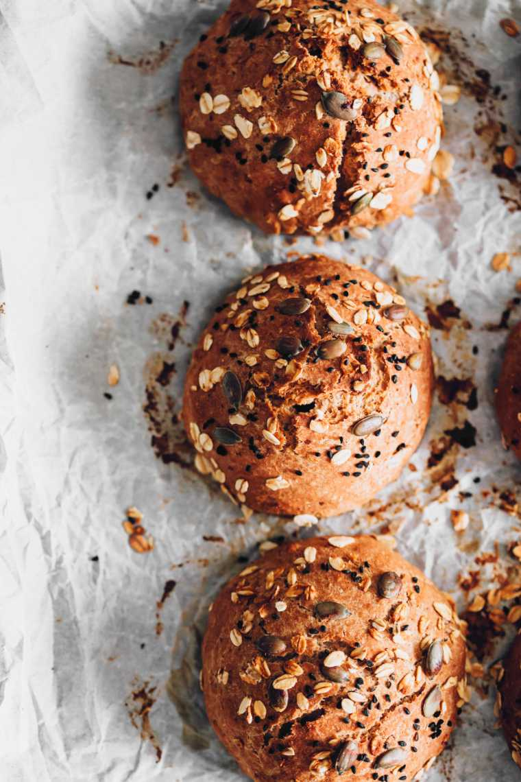 freshly baked whole wheat rolls topped with oats and seeds